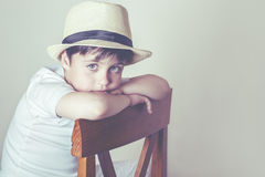 Sad child. Sad boy sitting in a chair Royalty Free Stock Images