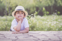 Sad child. Sad boy sitting in the field with hat Stock Image