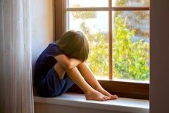 Sad child, boy, sitting on a window shield. Watching the sunset stock photos