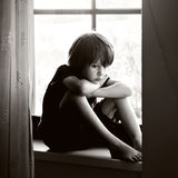 Sad child, boy, sitting on a window shield Royalty Free Stock Photography