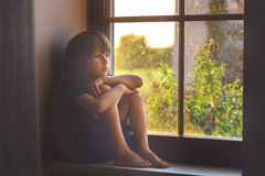 Sad child, boy, sitting on a window shield. Watching the sunset stock images