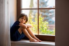 Sad child, boy, sitting on a window shield. Watching the sunset stock photography