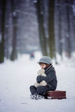 Sad child, boy, walking in a forest with old suitcase and teddy. Bear, wintertime in the snow Stock Images