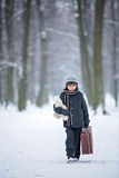 Sad child, boy, walking in a forest with old suitcase and teddy. Bear, wintertime in the snow Stock Photography