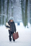 Sad child, boy, walking in a forest with old suitcase and teddy. Bear, wintertime in the snow Stock Photo