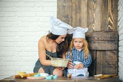 Sad child boy with woman in kitchen. Sad child boy with women in kitchen. Mother and toddler son in chef hats. Girl holding glass bowl with dough. Rolling pins stock photos