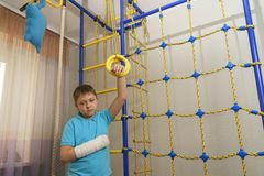 Sad child with a broken arm in the home environment . The cast on the hand of a little boy stock photos