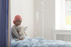 Sad child with cancer in the hospital with drip. Sad child with cancer hugging plush toy in the hospital with drip royalty free stock photography