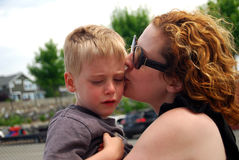 Sad child comforted by mother. Little boy crying after a fall at playground is comforted by his mother royalty free stock photos