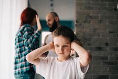 Sad Child Covering His Ears With Hands During Parents Quarrel. Stock Photos