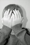 Sad child. Covers his face stock image