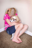 Sad child and dog sitting in corner. Sad child in corner hugging her dog for comfort stock photos