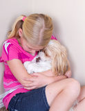 Sad child and dog sitting in corner. Sad child in corner hugging her dog for comfort stock image