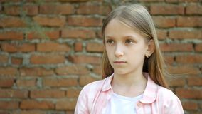 Sad child expression, unhappy girl portrait, depressed bored kid face.  stock video footage