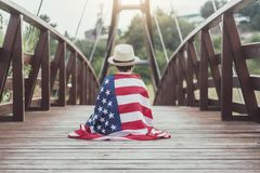 Sad child with the flag of the United States. On wooden bridge royalty free stock photo