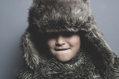 Sad child with fur hat and winter coat, cold concept and storm Royalty Free Stock Image