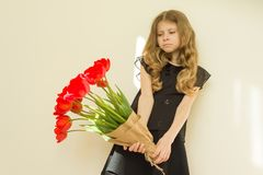 Sad child girl holding bouquet of flowers Stock Images