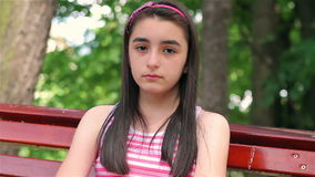 Sad child girl looking at camera. On bench in the park stock video