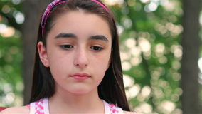 Sad child girl looking at camera close up. Sad child girl looking at camera in the park stock video