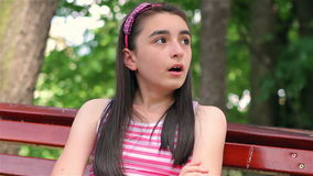 Sad child girl in park. Lonely sad child girl on a bench in the park looking around stock video