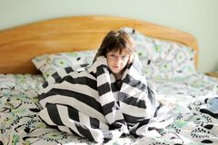 Sad child girl wrapped in blanket Stock Photos