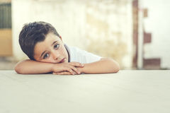 Sad child. With hands resting on a table Stock Photography