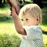 Sad Child hold the Parent Hand. Toned Photo of Sad Child hold the Adult Hand outdoor Royalty Free Stock Photography