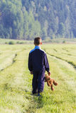 Sad child is holding a brown teddy bear in the meadow. Back view. Copy space. Sadness, fear, frustration, loneliness. Sad childy is holding a brown teddy bear in Stock Photography