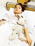 Sad child on hospital bed. Holding rabbit toy royalty free stock photography