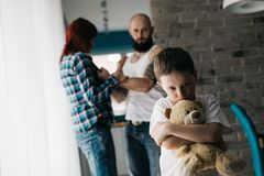 Sad child hugging his teddy bear during parents quarrel. Man about to beat his wife Royalty Free Stock Photo