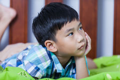 Sad child inside bedroom. Problem families concept. Sad child inside bedroom. Close up handsome asian boy lying on his bed looking sad and lonely. Problem Royalty Free Stock Photography