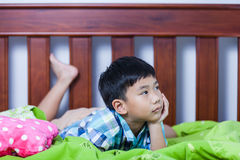 Sad child inside bedroom. Problem families concept. Sad child inside bedroom. Handsome asian boy lying on his bed looking sad and lonely. Problem families Stock Photo