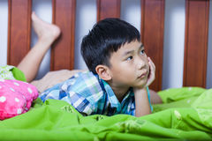 Sad child inside bedroom. Problem families concept. Sad child inside bedroom. Handsome asian boy lying on his bed looking sad and lonely. Problem families Royalty Free Stock Photo