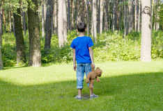 Free Sad Child Is Holding A Brown Teddy Bear And Standing On The Meadow. Back View. Copy Space. Sadness, Fear, Frustration Stock Images - 76769544