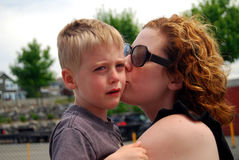 Sad child kissed by mother. Little boy upset after a fall at playground is kissed to make it all better by his mother Stock Image