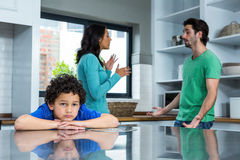 Sad child listening to parents argument. In the kitchen Stock Photos