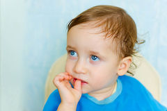Sad child looking away. And takes fingers in his mouth royalty free stock images