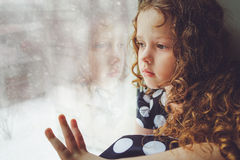 Sad child looking out the window. Toning photo. Royalty Free Stock Image
