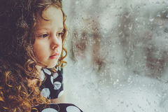 Sad child looking out the window. Toning photo. Sad child looking out the window on falling snow. Toning photo stock photography