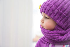 Sad child looking into the window during cold winter day in warm clothes stock photography