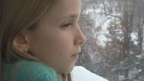 Sad Child Looking on Window, Unhappy Thoughtful Kid, Girl Face, Snowing Winter stock image