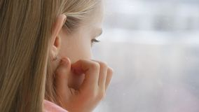 Sad Child Looking on Window, Unhappy Thoughtful Kid, Girl Face, Snowing Winter.  royalty free stock photos