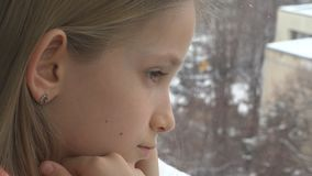 Sad Child Looking on Window, Unhappy Thoughtful Kid, Girl Face, Snowing Winter.  royalty free stock photography