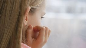 Sad Child Looking on Window, Unhappy Thoughtful Kid, Girl Face, Snowing Winter.  royalty free stock image