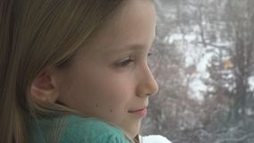 Sad Child Looking on Window, Unhappy Thoughtful Kid, Girl Face, Snowing Winter.  stock photography