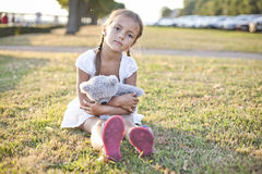 Sad child in a park. Young lonely girl sit on a grass in a park with her toy teddy bear Royalty Free Stock Photography