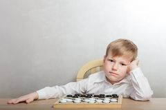 Sad child playing checkers at the table stock image