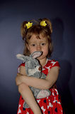 Sad child with plush toy close up on a blue background. Stock Images