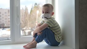 Sad child in protective medical masks lonely sitting near window. Quarantine, staying at home. Slow motion, handheld.
