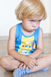 Sad child sitting with arms across. Kid with guilty sulky look sitting at home on the floor Royalty Free Stock Photos